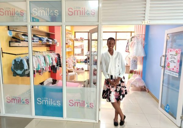 Linda Grace Rugema poses in front of her storefront, Little Smiles